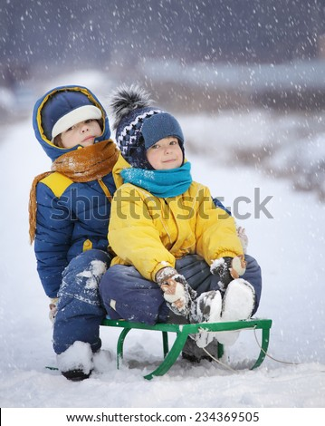 two  happy boys on sled outdoors winter snow - stock photo