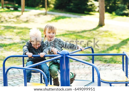 Two happy boys playing on playground in the park.
