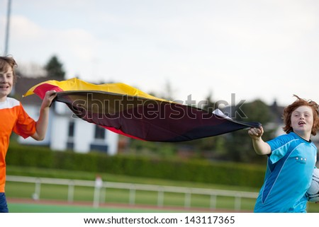 two happy boys running on soccer field with german flag - stock photo