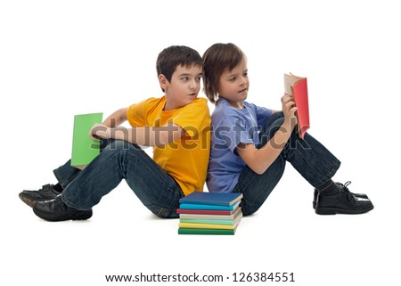 Two happy boys sitting on the floor and reading books