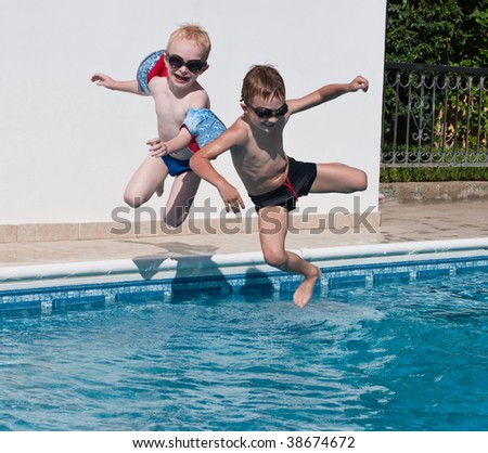 two happy brothers jumping into swimming pool - stock photo