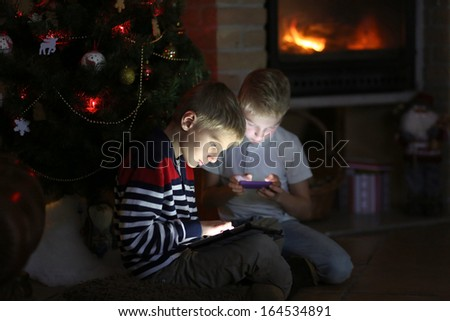 Two happy brothers sitting at the fireplace on a cozy winter evening nearby the christmas tree choosing gifts from online catalog or playing with tablet pc and smart phone - stock photo