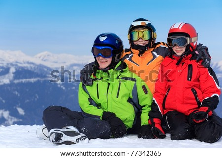 Two happy brothers with sister in ski helmets and goggles on snowy Alpine mountain.