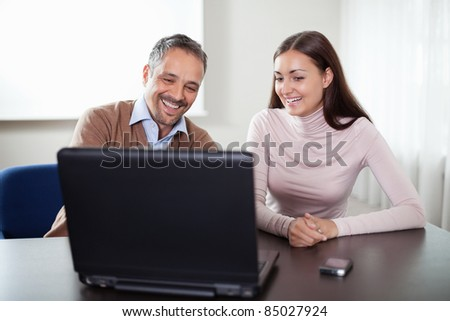 Two happy business colleagues working on laptop - stock photo