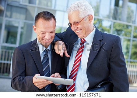 Two happy business men working together on a tablet computer - stock photo