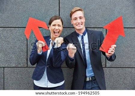 Two happy business people cheering with big red arrows pointing up - stock photo