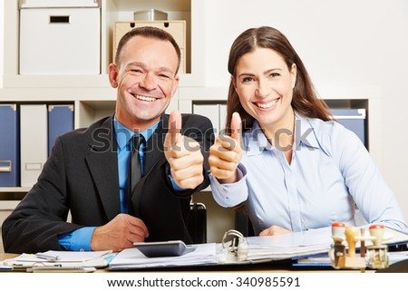 Two happy business people in office holding their thumbs up - stock photo