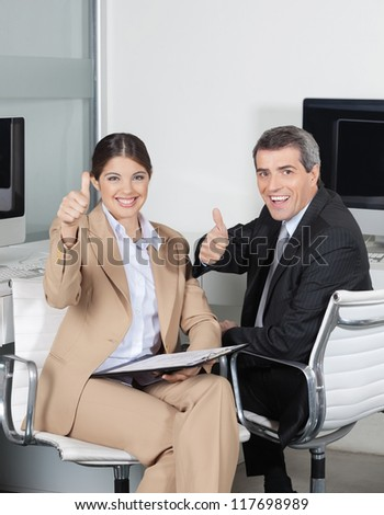 Two happy business people in the office holding their thumbs up - stock photo