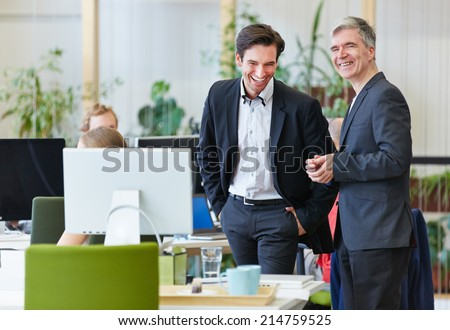 Two happy business people laughing during office break - stock photo