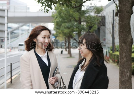 Two happy business women talking on the city street