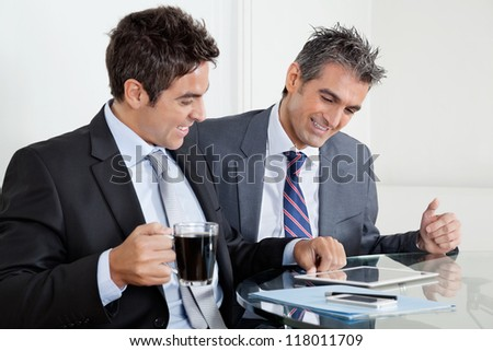 Two happy businessmen using digital tablet at desk in office - stock photo