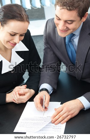 Two happy businesspeople signing document at office