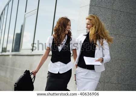 two happy businesswoman laughing while solving some problems - stock photo