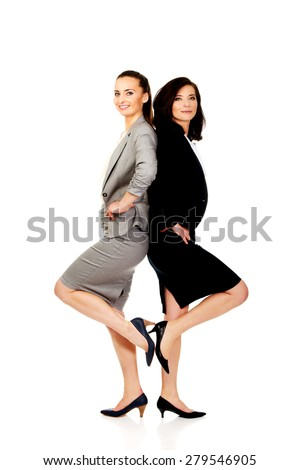 Two happy businesswomen leaning on each other. - stock photo