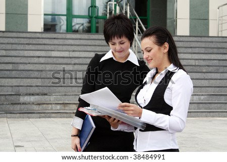 Two happy businesswomen with paper chart (focus on women with papers) - stock photo