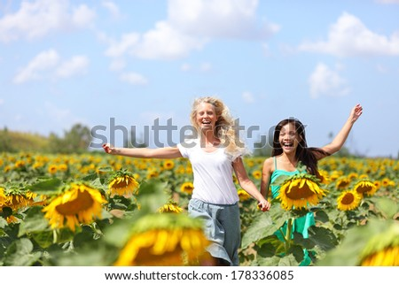 Two happy carefree young women running through field of sunflowers on a sunny summer day laughing and having fun with arms in the air. Beautiful young multiracial girlfriends, Asian and Caucasian girl - stock photo