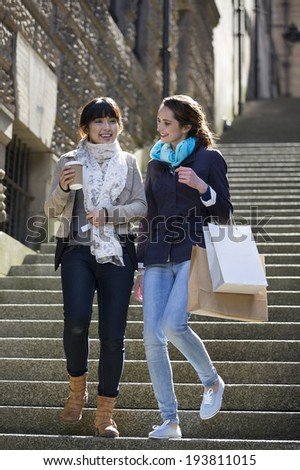 Two happy Caucasian and Asian women shopping together, having fun and laughing.