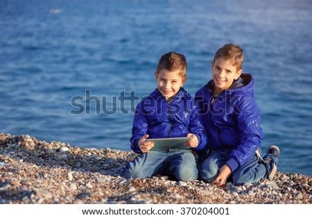 Two happy caucasian kids, brothers, holding digital tablet pc sitting outdoors at pebble beach against the sea - stock photo