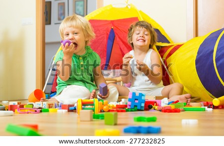 Two happy cheerful siblings playing with toys together at home