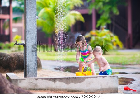 Two happy children, adorable baby boy and a little toddler girl in swimming suits playing in an outdoor shower in a tropical resort during summer vacation - stock photo