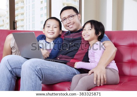 Two happy children and their father with laptop computer and smiling at the camera while sitting on the couch in the apartment