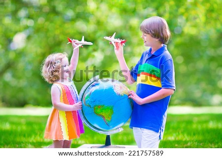 Two happy children, cute curly toddler girl and a smiling school age boy playing with toy airplanes flying over the globe dreaming of travelling around the world - stock photo