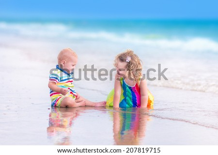 Two happy children, cute curly toddler girl and funny baby boy, brother and sister, playing together digging sand in water on a beautiful beach enjoying a hot summer vacation day on a tropical island - stock photo