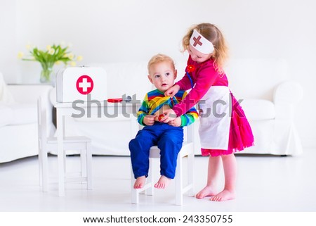 Two happy children, cute toddler girl and adorable baby boy, brother and sister, playing doctor and hospital using stethoscope toy and medical uniform, having fun at home or preschool - stock photo