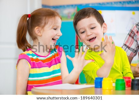 Two happy children drawing with colorful paints on palms - stock photo