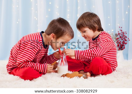 Two happy children eating cookies at christmas and drinking milk, laughing and talking, having fun - stock photo