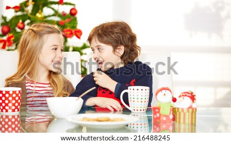 Two happy children eating cookies at christmas at the table - stock photo