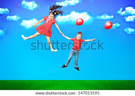 Two happy children flying together on balloons in a bright summer day. - stock photo