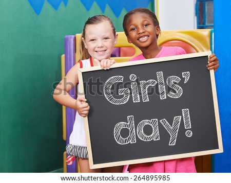 Two happy children holding a blackboard for the Girls' Day - stock photo