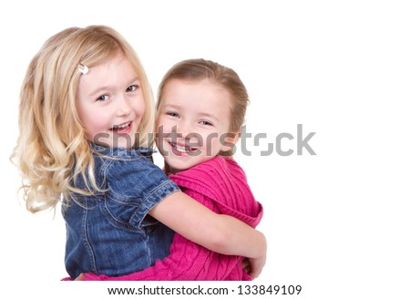Two happy children hugging each other on an isolated white background