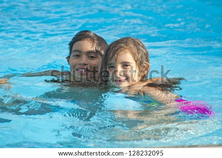 Two happy children in the swimming pool. - stock photo