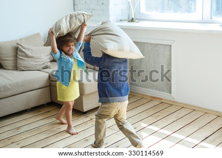 Two happy children is fighting a pillows each other at home - stock photo