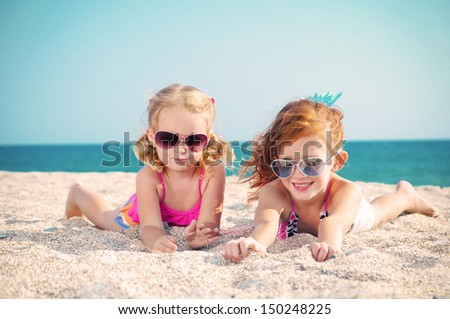 Two happy children lying on the sand by the sea - stock photo