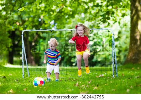 Two happy children playing European football outdoors in school yard. Kids play soccer. Active sport for preschool child. Ball game for young kid team. Boy and girl score a goal in football match. - stock photo