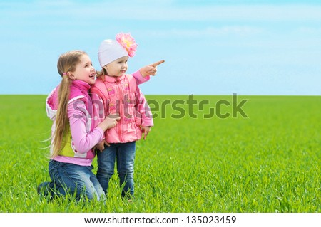 Two happy children playing in a meadow - stock photo