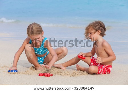 Two happy children  playing on the beach at the day time. - stock photo