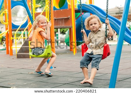 Two happy children playing on the playground at the day time. Concept brother and sister forever. - stock photo