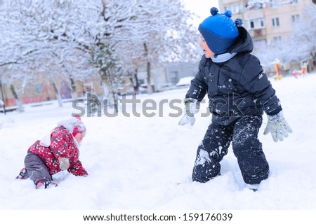 Two happy children playing snowball on snowy field - stock photo