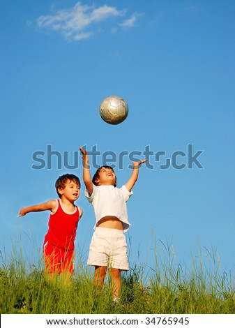 Two happy children playing with a ball on meadow - stock photo