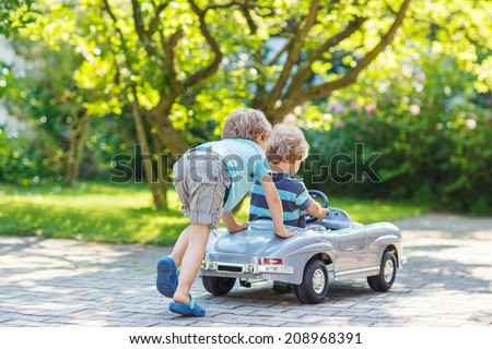 Two happy children playing with big old toy car in summer garden, outdoors. - stock photo