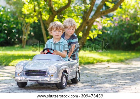 Two happy children playing with big old toy car in summer garden, outdoors.  Family, childhood, lifestyle concept.