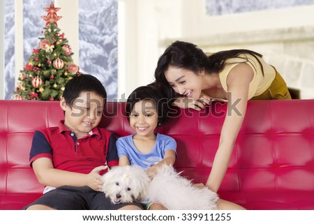 Two happy children sitting on the sofa while playing a dog with their mother at home, shot with a christmas tree background - stock photo