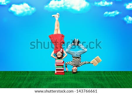 Two happy children standing on their heads on books. Educational concept. - stock photo