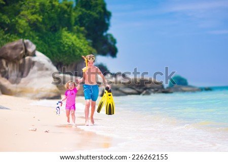 Two happy children, teenager boy and a little toddler girl, brother and sister, running on a beautiful tropical beach after snorkeling in the ocean having fun during summer vacation