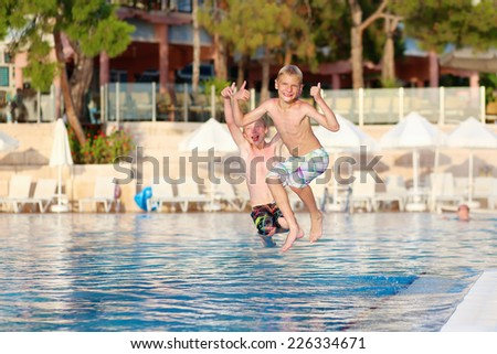 Two happy children, twin brothers are jumping into swimming pool at the resort at sunset - stock photo