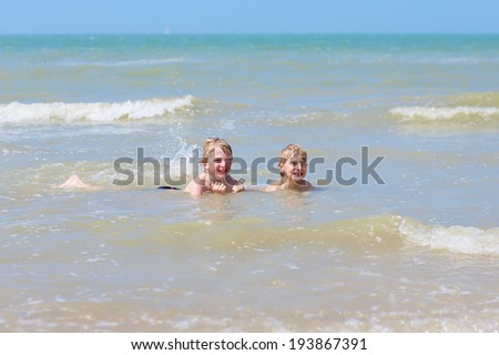 Two happy children, twin brothers, blonde school boys playing on the beach jumping and splashing in the sea on a sunny summer day - stock photo